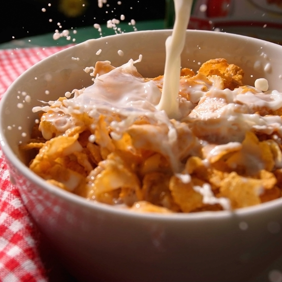 Milk being poured on corn flakes