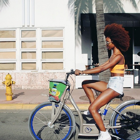 Black woman with afro riding a bike under palm tree