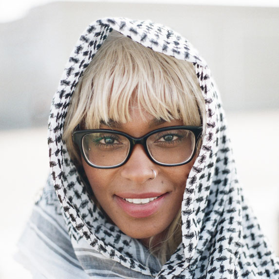 Black woman wearing headscarf and wearing glasses