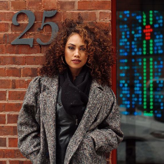 Black woman with curly hair standing outside of building