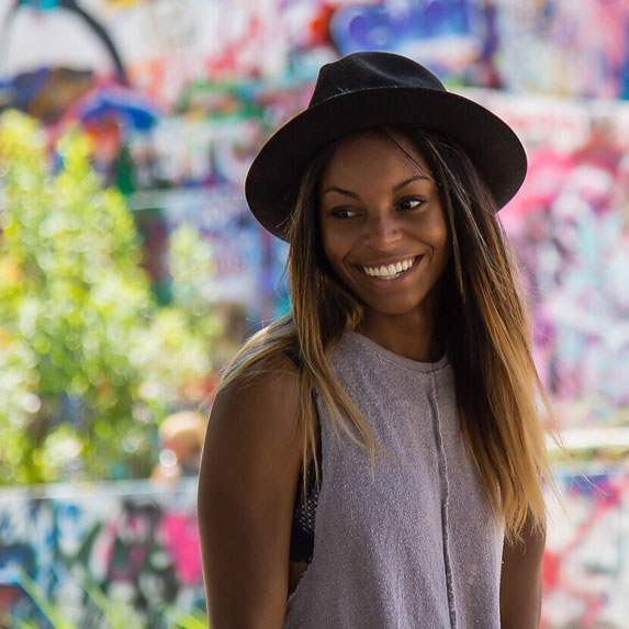 Black woman wearing a hat in front of colourful background