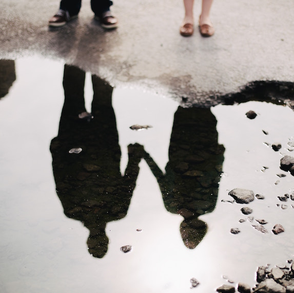Couples' shadow is visible in a pool of water by their feet