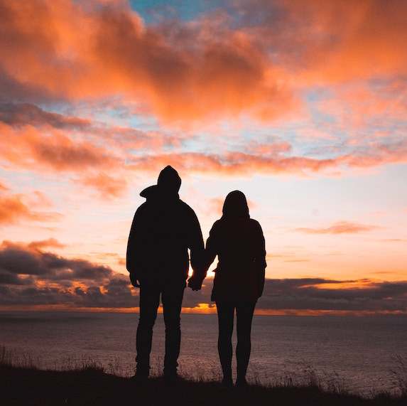 Silhouette of a couple holding hands and standing together at sunset