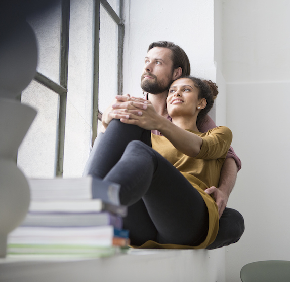 Couple sits together on a windowsill