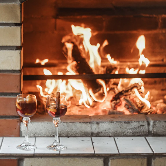 Drinks by a fireplace