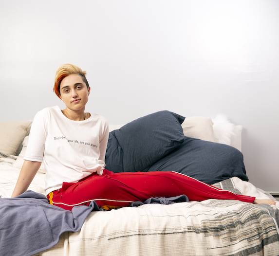 Individual sitting on a bed