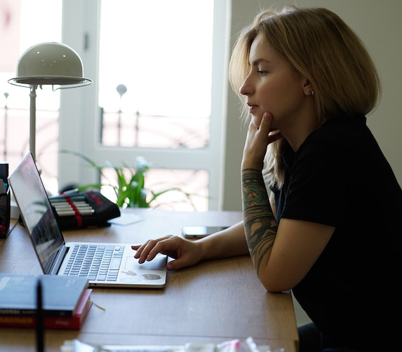 Woman looks thoughtful as she browses the Internet on her laptop