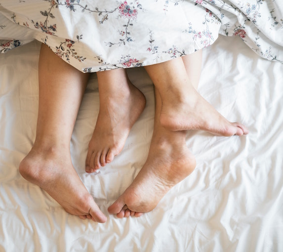 Pair of feet intertwined in bed