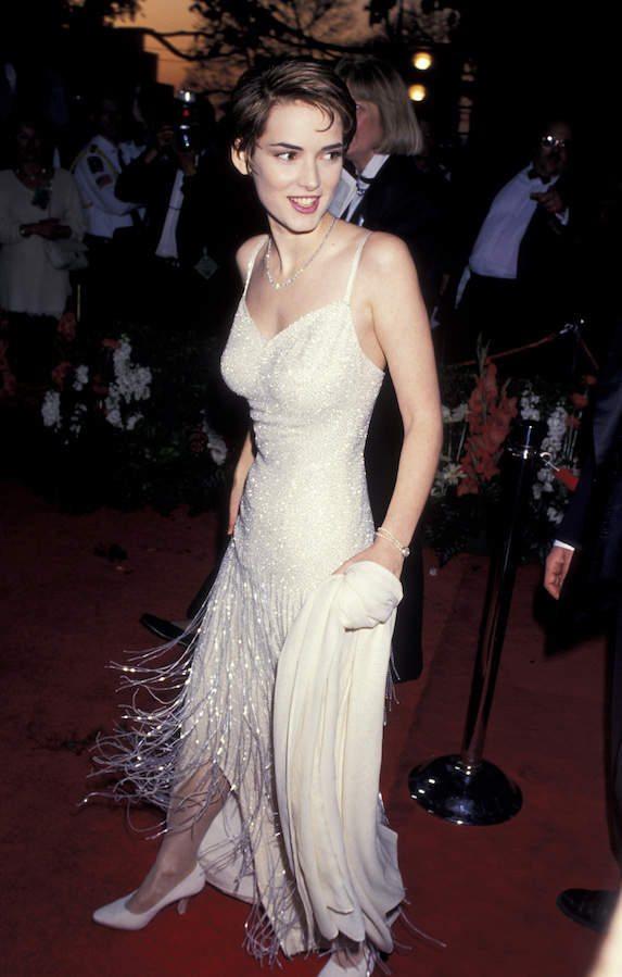 Winona Ryder wears a beaded floor-length white gown with fringe details to the 1994 Academy Awards
