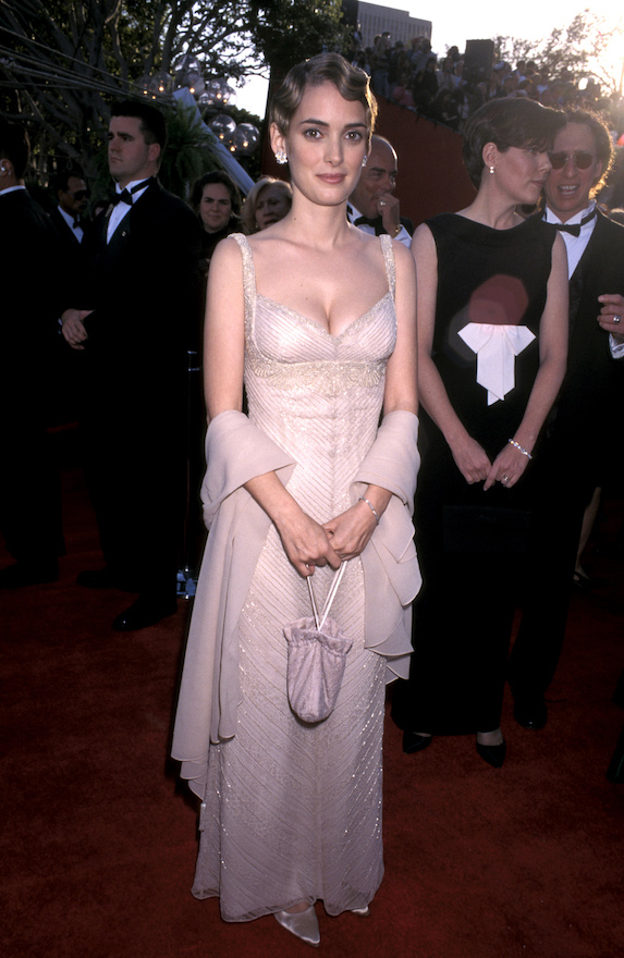 Winona Ryder wears a blush floor-length gown with beading details to the 1996 Academy Awards