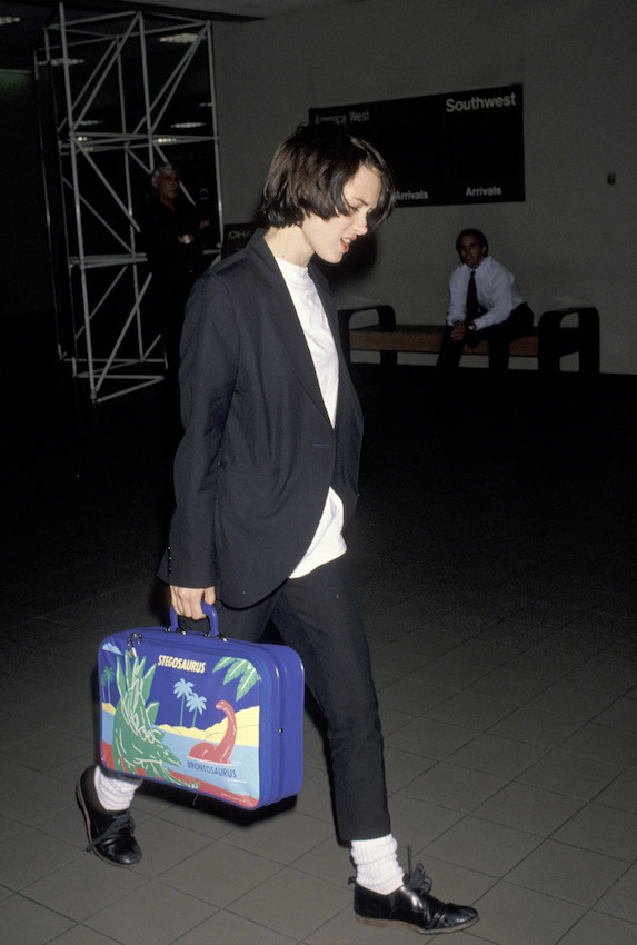 Winona Ryder wears a suit with an oversized white tee while at Los Angeles International Airport in 1990