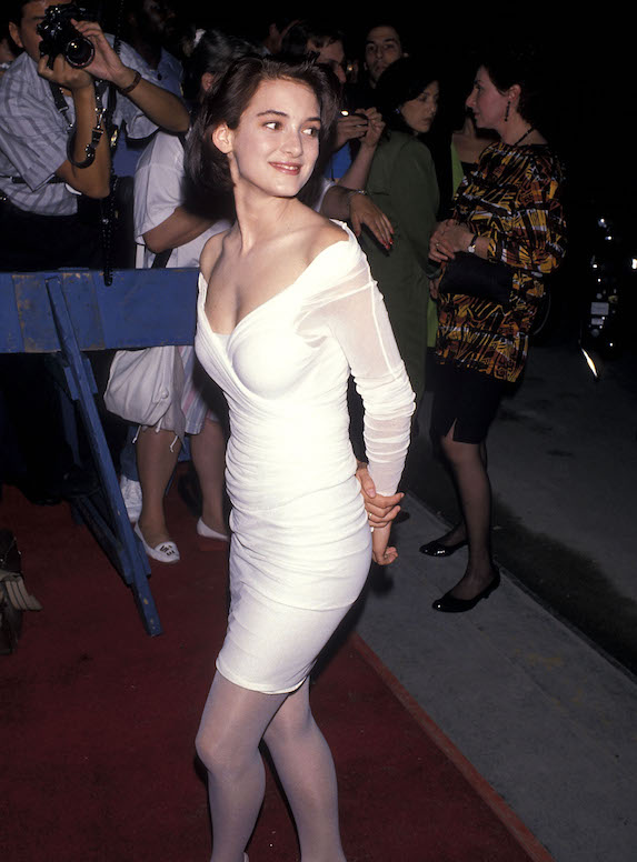 Winona Ryder wears a white dress and stockings at a film premiere in 1989