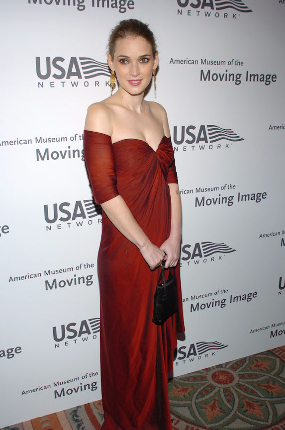Winona Ryder wears a red off-the-shoulder gown while attending a benefit event in 2004