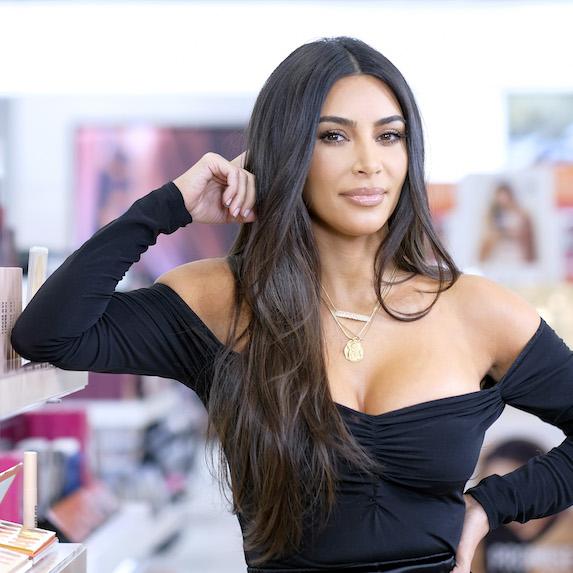 Kim Kardashian posing, leaning against an edge