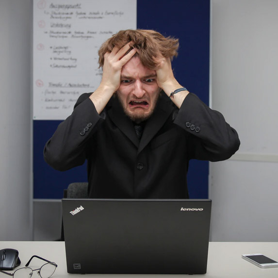 man with head in hands and frustrated expression