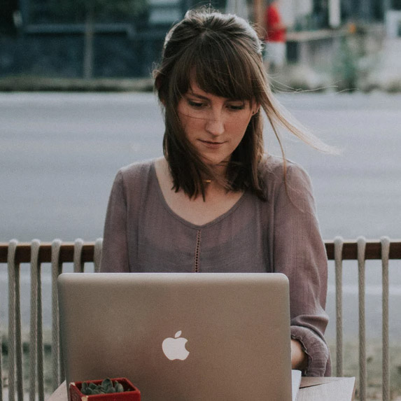 woman sitting outside with macbook