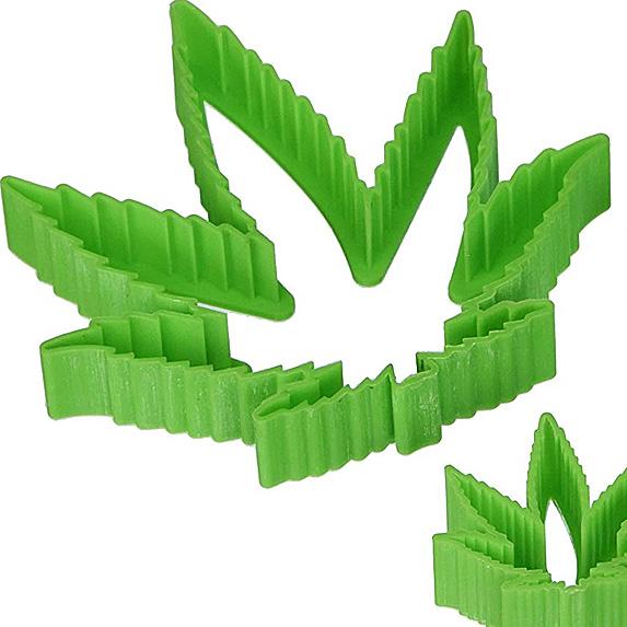 Green plastic cookie cutter shaped like cannabis leaf