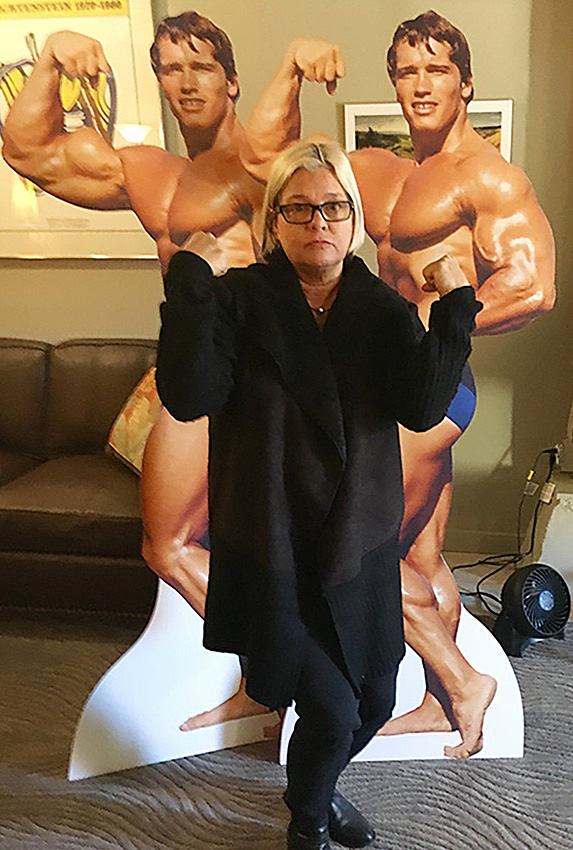 Woman standing in front of two cardboard cutouts of Arnold Schwarzenegger