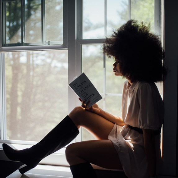 Woman sitting on a window sill, reading a book