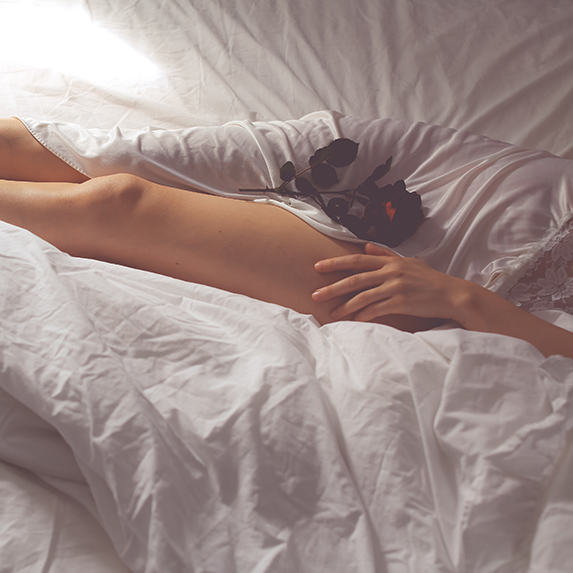 Woman's legs on bed with a rose
