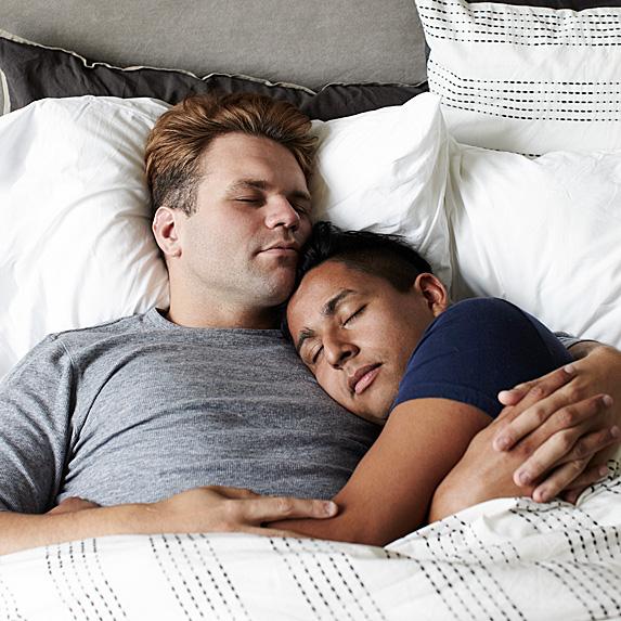 Two men sleeping in bed