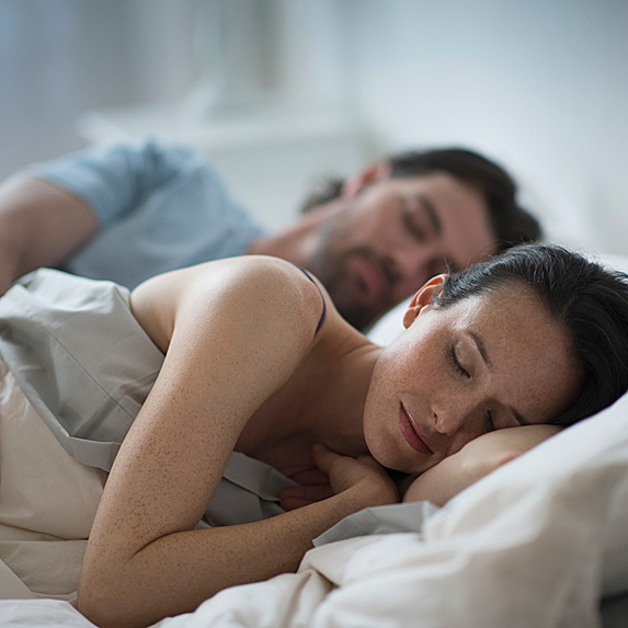 Man and freckled woman in bed sleeping
