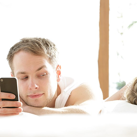Man in bed, with his smartphone out, glancing sneakily sideways