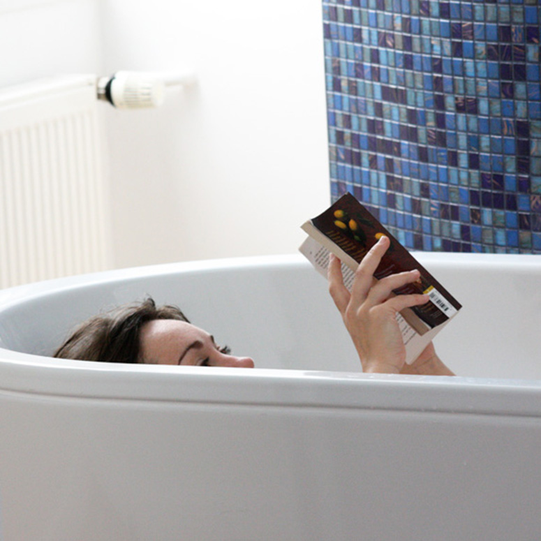 Woman reading a book in her tub