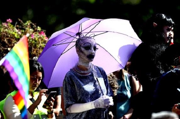 Drag performer in makeup under an umbrellla
