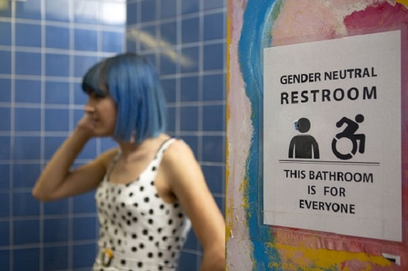 Person with blue hair in doorway of all-gender washroom