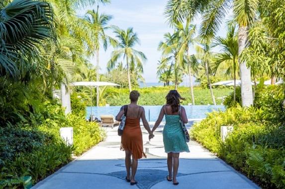 women walking towards tropical beach holding hands