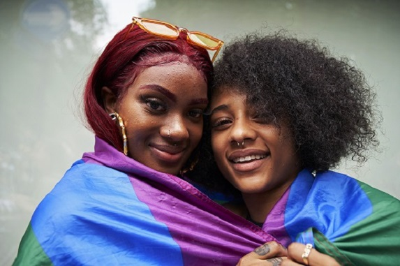two women wrapped in rainbow pride flag