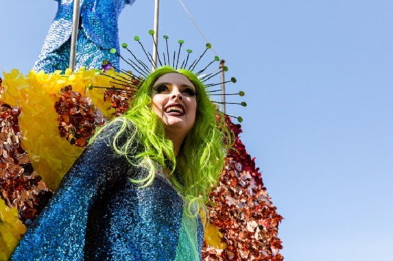 person in drag standing on a float