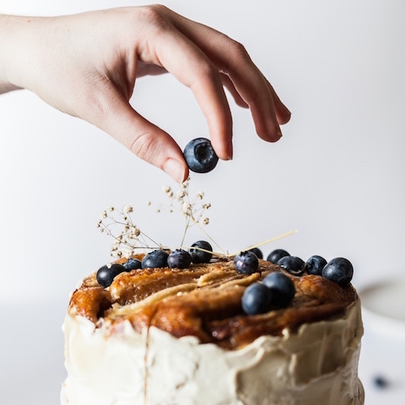hand putting a blueberry on top of a white cake