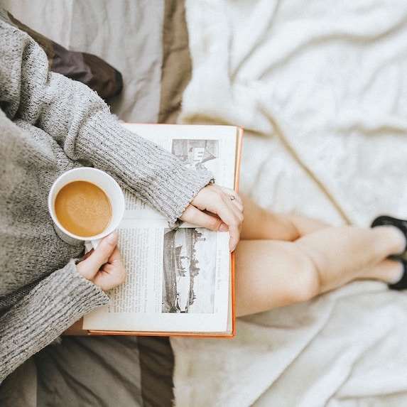 woman reading book with cup of coffee on lap