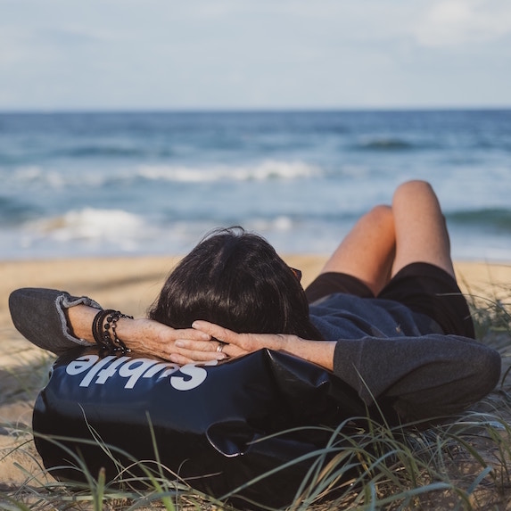 woman laying on beach in front of ocean