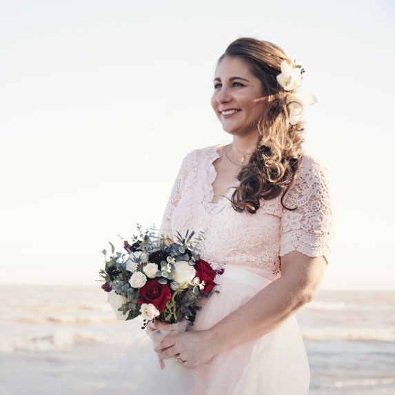 A bride walking with a bouquet at an outdoor venue