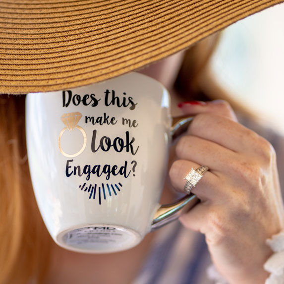 A woman taking a sip from a mug that says
