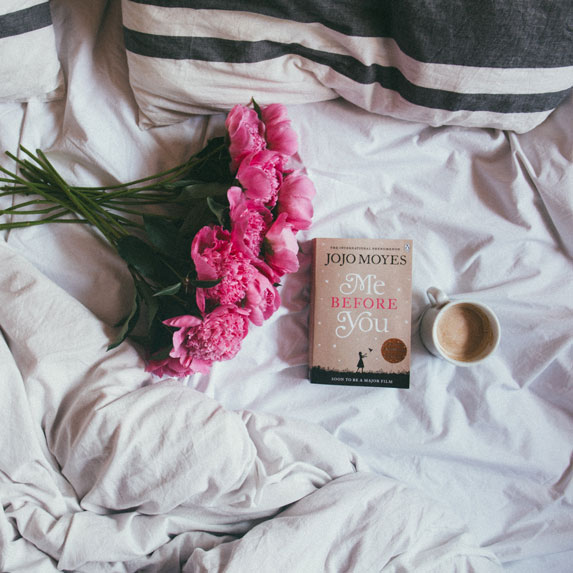 A bouquet, with a coffee mug, and book entitled