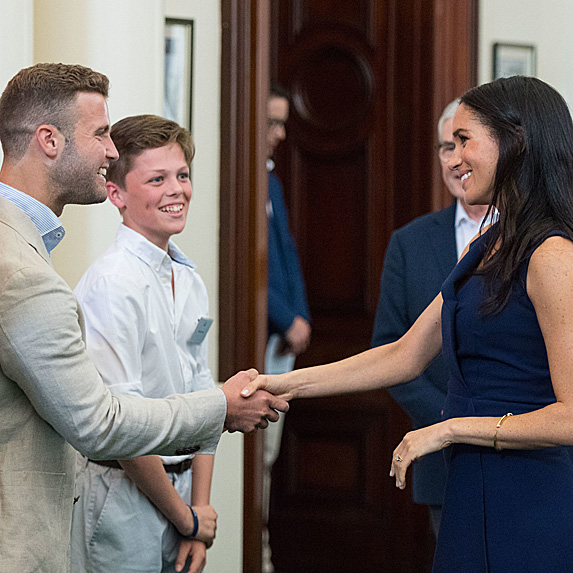 Duchess Meghan shaking hands with man