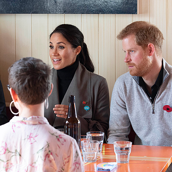 Duchess Meghan and Prince Harry speaking with people at cafe