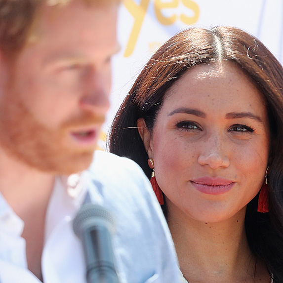 Prince Harry speaking while Duchess Meghan looks on