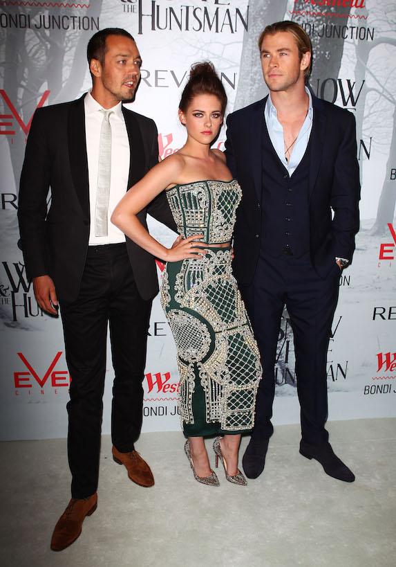 Kristen Stewart wears an embellished two-piece outfit as she stands between director Rupert Sanders and co-star Chris Hemsworth at a film premiere in Australia