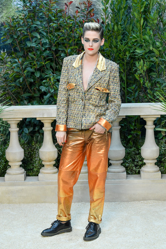 Kristen Stewart wears a low-cut blazer with metallic-coloured cuffed pants and masculine shoes to a Chanel photo-call in 2019