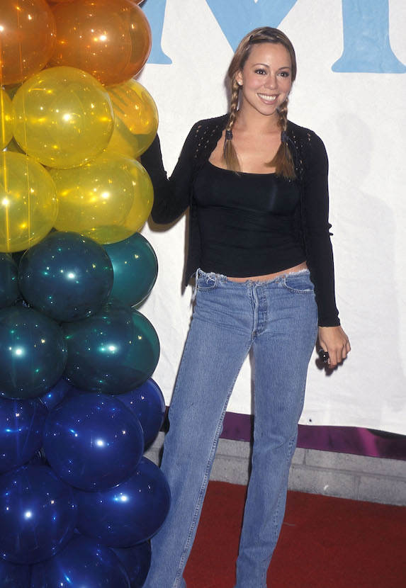Mariah Carey wears her hair in braids and sports a black cardigan and tank top with jeans at an album signing