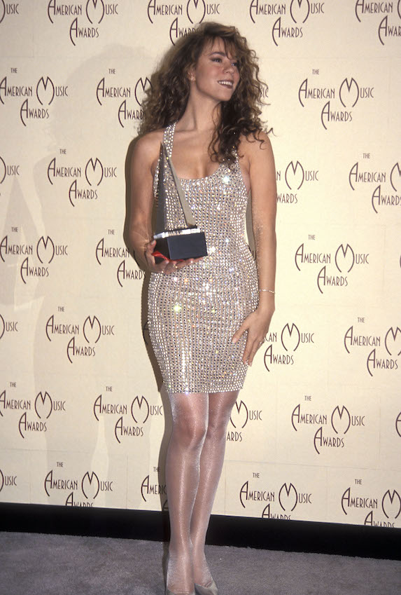 Maria Carey wears a sparkly mini dress and tights while holding an award at the American Music Awards in 1992