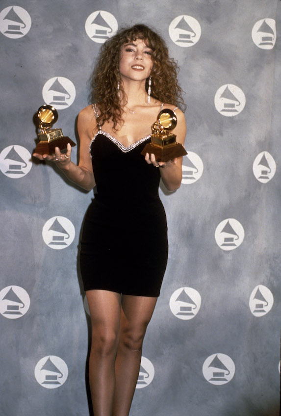 Mariah Carey wears a black mini dress while holding awards and posing for photographs at the 1991 Grammy Awards