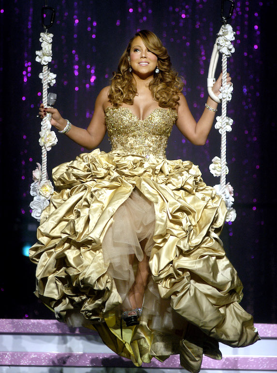 Mariah Carey wears a gold gown while sitting on a rope swing while in concert in 2010