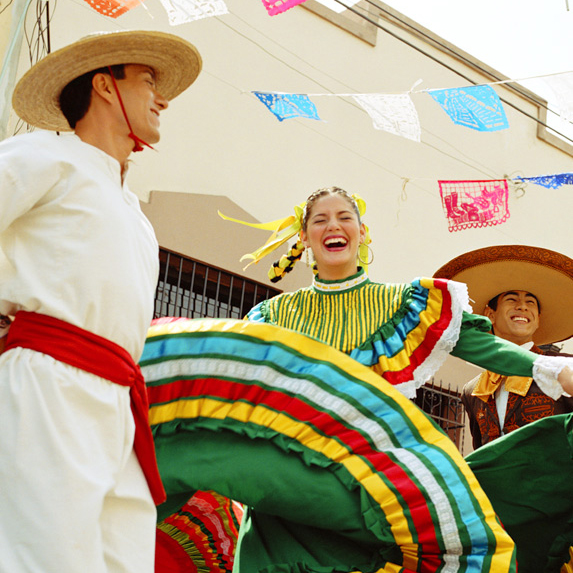 A Mexican dancer spins in her colourful dress while the Mariachi band plays on
