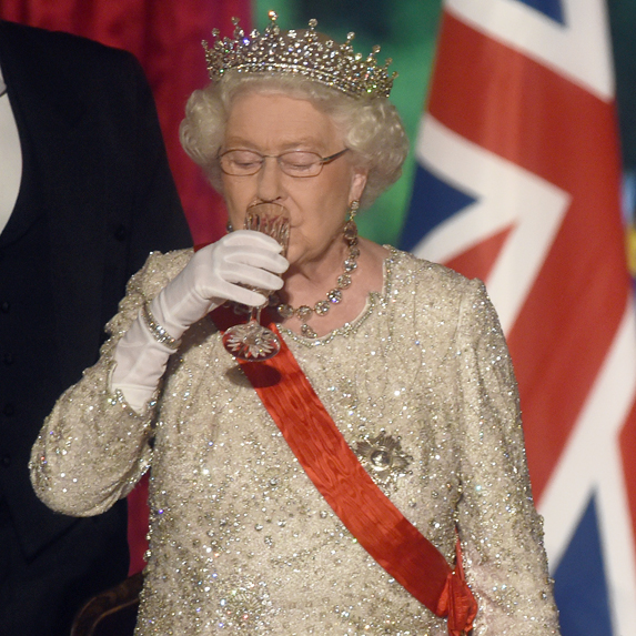 Queen Elizabeth takes a sip of an alcoholic beverage at a royal event